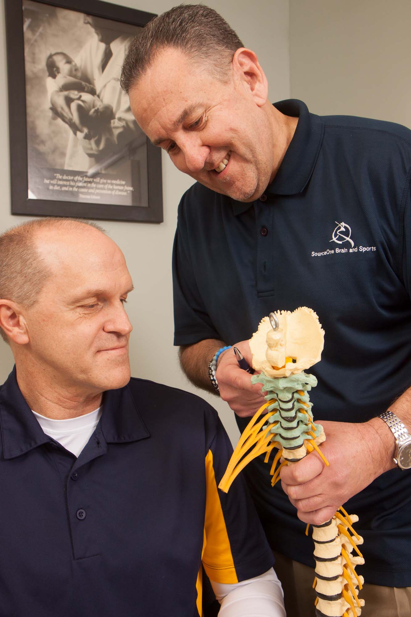 Dr. Bubanic pointing to model spine with patient